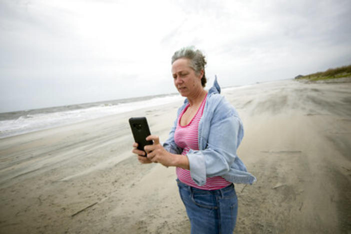 Crystal Travaille takes a cell phone photo of the wind and seas on the beach as Hurricane Dorian makes its way up the east coast, Wednesday, Sept. 4, 2019, in Tybee Island.