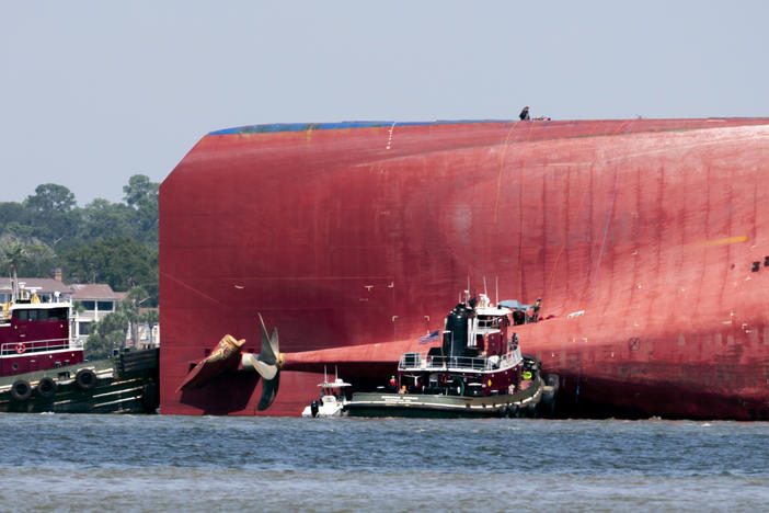 Rescuers work near the stern of the vessel Golden Ray as it lays on its side near the Moran tug boat Dorothy Moran, Monday, Sept. 9, 2019, in Jekyll Island, Ga.