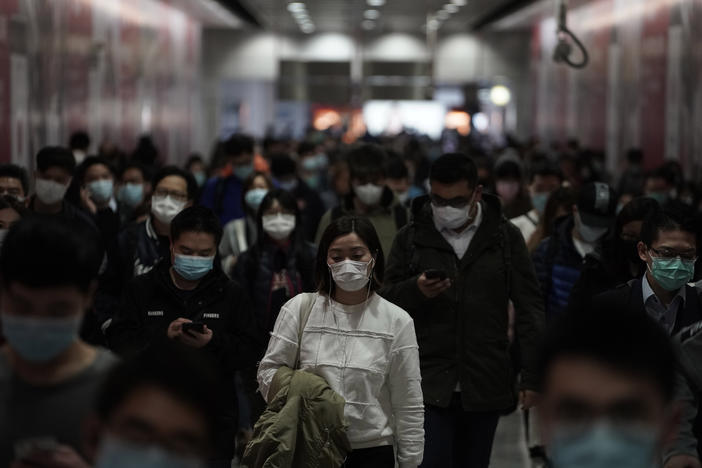 People wearing masks, walk in a subway station, in Hong Kong, Friday, Feb. 7, 2020. Hong Kong on Friday confirmed 25 cases of a new virus that originated in the Chinese province of Hubei. According to the latest figures, 233 new cases of the novel coronav