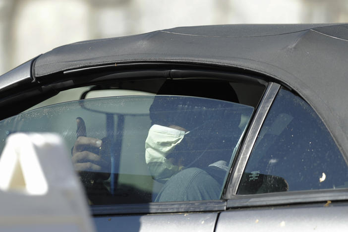 A person wearing a mask rolls down the window to ask about a COVID-19 testing site on Georgia Tech's campus, Monday, April 6, 2020, in Atlanta.
