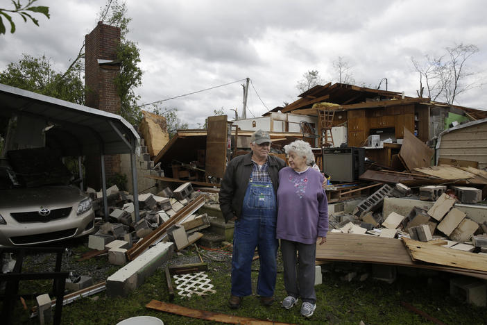 Emma, 78, right, and husband Charles Pritchett, 80, stand in front of their home the day after a tornado hit, Monday, April 13, 2020, in Chatsworth, Ga.