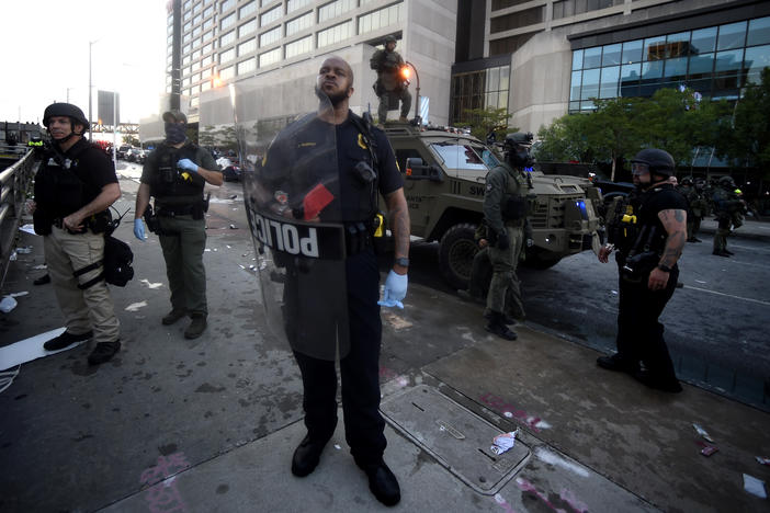 An Atlanta police officer stands near where police officers and protesters clashed near CNN Center, Friday, May 29, 2020 in Atlanta. The protest started peacefully earlier in the day before demonstrators clashed with police.