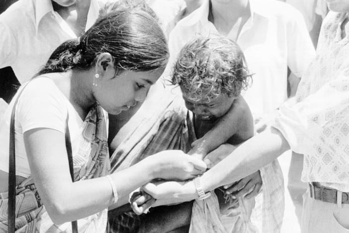 Two members of an Indian medical team get together to vaccinate a small child against smallpox at Hakegora village in India's Bihar state, June 23, 1974.
