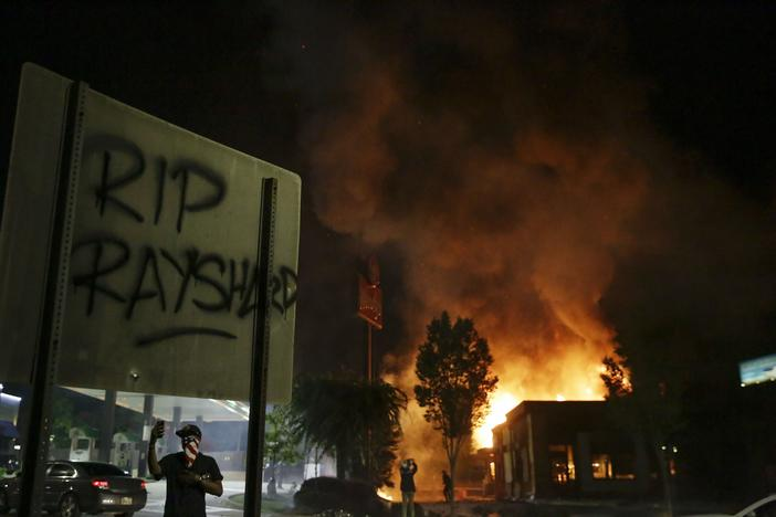 "In this Saturday, June 13, 2020 file photo, ""RIP Rayshard"" is spray-painted on a sign as flames engulf a Wendy's restaurant where Rayshard Brooks was shot and killed by police in Atlanta."