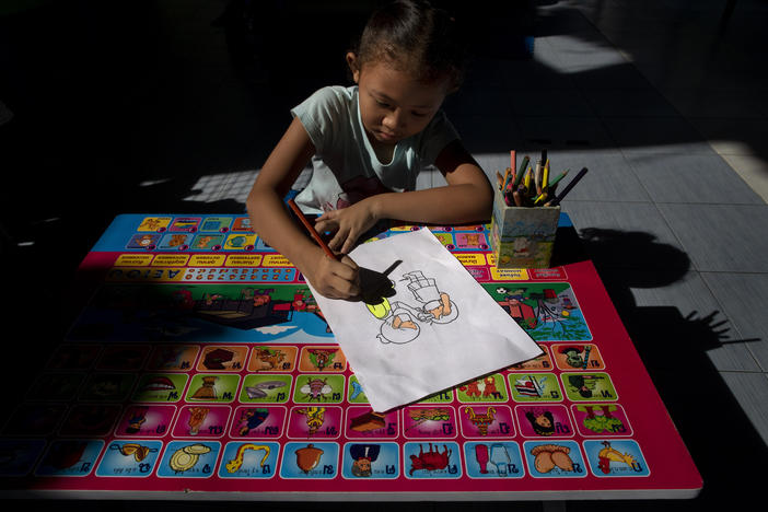 Warisara Klawkla, a daughter of teacher Watcharee Klawkla, colors a drawing made to educate children on COVID-19 prevention methods while her mother help cooking a meal at Makkasan preschool in Bangkok, Thailand, Wednesday, June 24, 2020.
