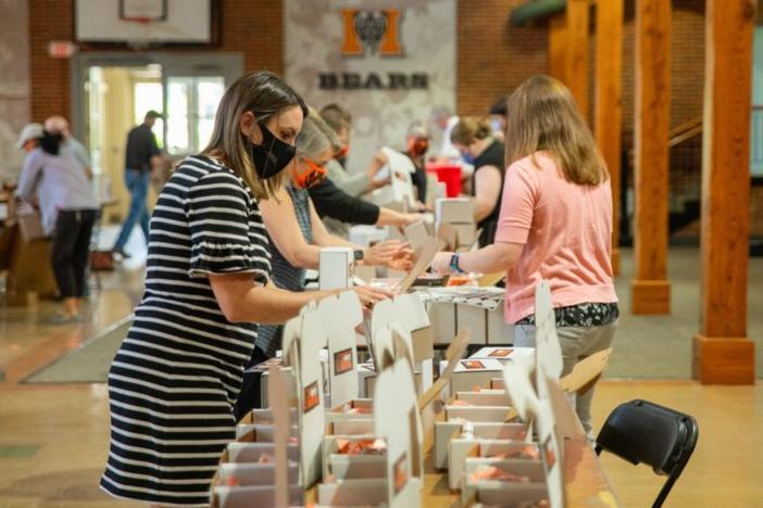 Volunteers from Mercer University assemble Bears Care kits to hand out to students attending summer classes. Students returning in the fall will also receive the kits.