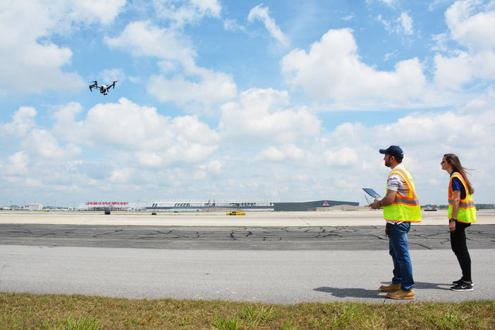 Jim Duguay and Katie Eleam pilot a drone over runway 27R at Hartsfield-Jackson Atlanta International Airport.