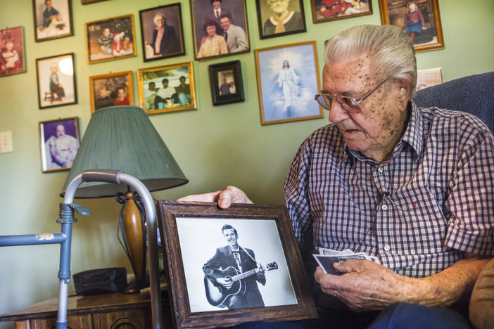 In the living room of his Macon, Ga. home, Jimmy Haney holds a photo of himself taken in the days when he played the Grand Ole Opry. Haney was once rhythm guitarist for Patsy Cline.