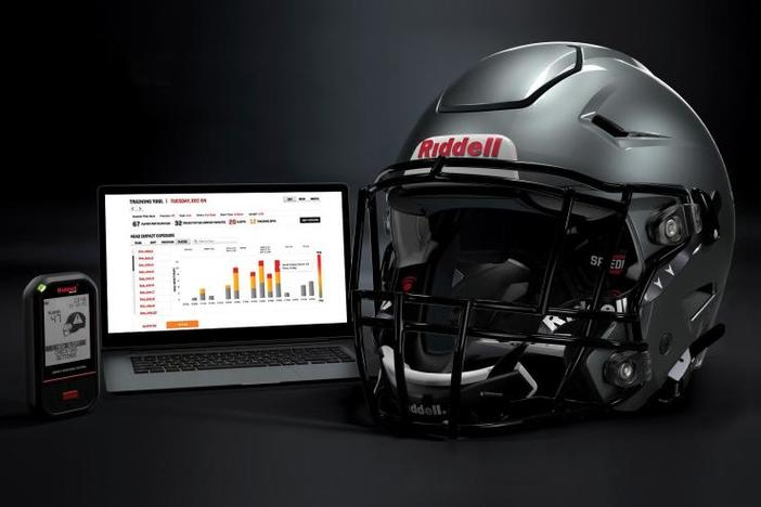 In this May 2020 photo provided by Riddell, a Riddell SpeedFlex helmet sits next to a computer screen displaying information from the InSite tool.