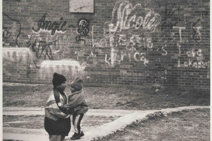 "A man and child next to a wall full of graffiti in the East Lake area of Atlanta, 1996. The documentary ""East Lake Meadows: A Public Housing Story"" airs on PBS on Tuesday, Mar. 24 at 8 p.m."