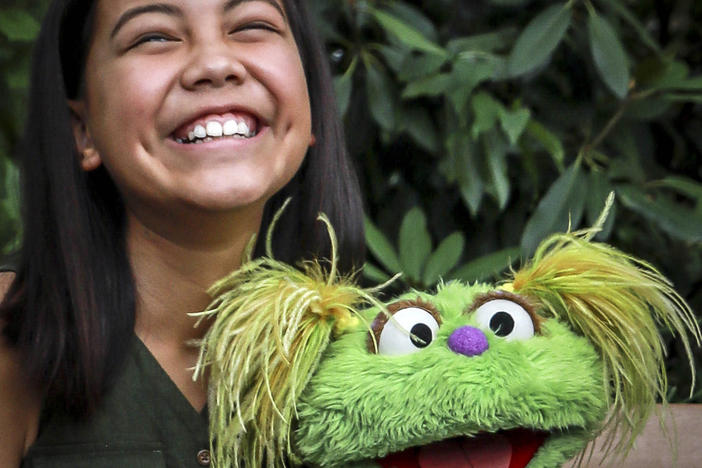 "10-year-old Salia Woodbury pictured, whose parents are in recovery, with ""Sesame Street"" character Karli in New York. Sesame Workshop is addressing the issue of addiction."