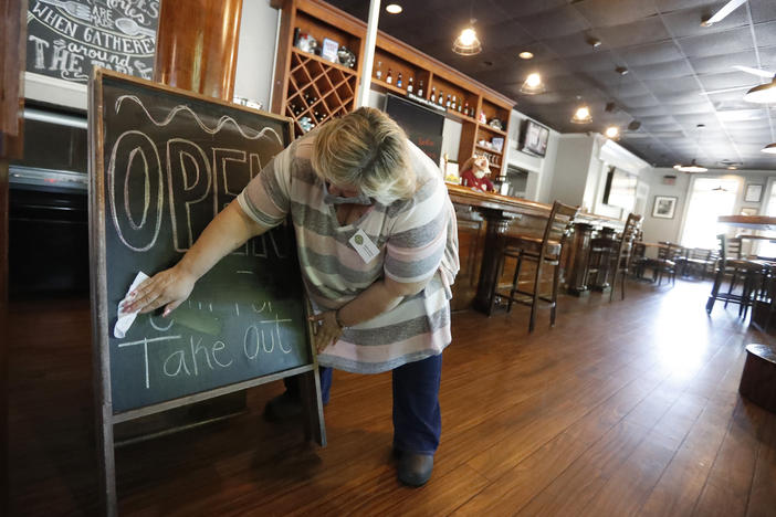 Mary Spoto, general manager of Madison Chop House Grille, changes the sign as she and her staff prepare to shift from take out only to dine-in service in April in Madison, Ga.