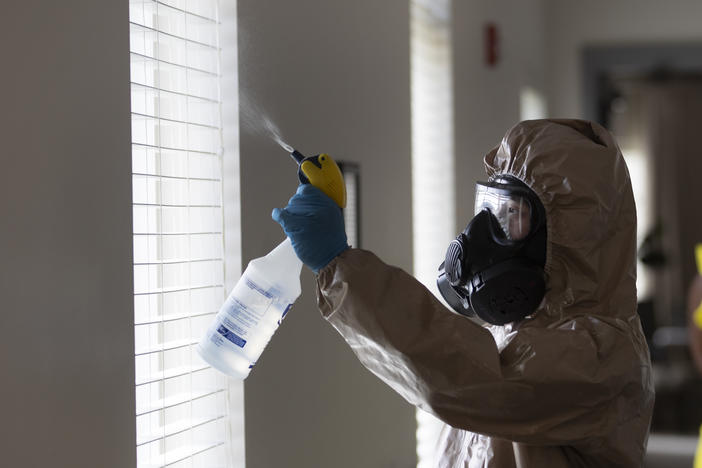 A member of the Georgia National Guard works to clean and disinfect hallways and common areas at Provident Village assisted living and memory care home, Tuesday, May 5, 2020, in Smyrna, Ga. There have been no cases among residents or staff there.