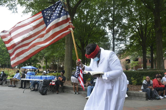 A woman clutching an American flag and a Bible stands outside the funeral of Rayshard Brooks on Tuesday.