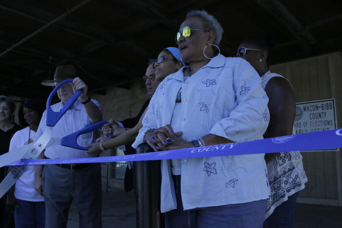 Macon-Bibb Board of Elections Chair Cassandra Powell (in foreground) with local leaders and other elections officials cutting the ribbon to open a new early voting election space at the city's bus terminal.