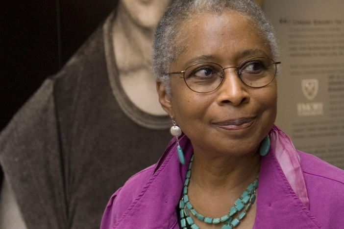 Alice Walker stands in front of a picture of herself from 1974 as she tours her archives at Emory University, in Atlanta.
