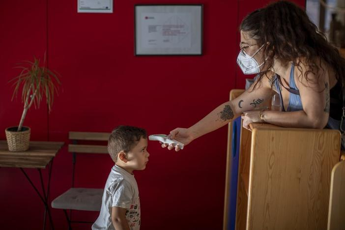 Hugo, 3, has his temperature taken by a teacher as he arrives at Cobi kindergarten in Barcelona, Spain, Friday, June 26, 2020.