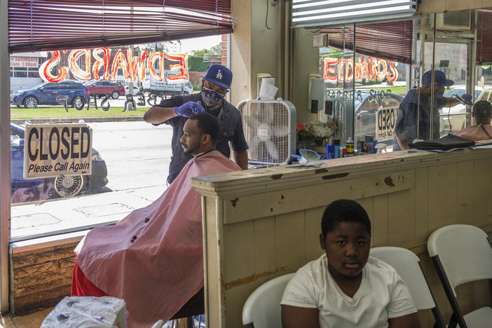 "Barber Marian Searcy cuts Shaquille Sanders' hair in the shop Searcy helps run in downtown Macon Friday. ""Just me being a man and the stress of me being a man, to provide for my household, that's my drive for coming back to work,"" Searcy said."