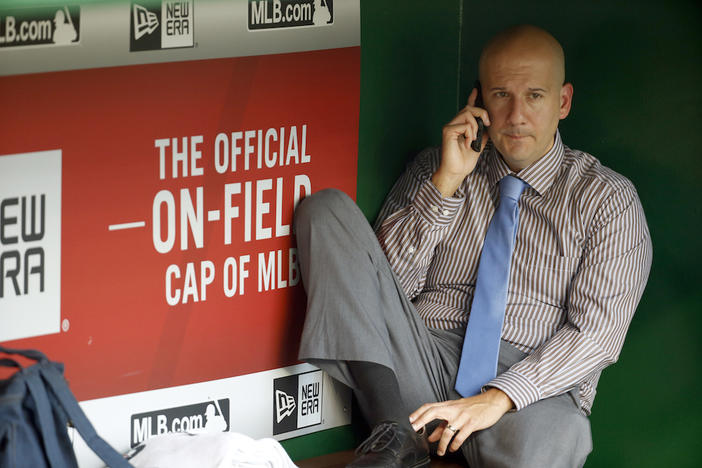 John Coppolella talks on the phone in the dugout during batting practice before a baseball game against the Washington Nationals at Nationals Park, Friday, Sept. 4, 2015, in Washington.