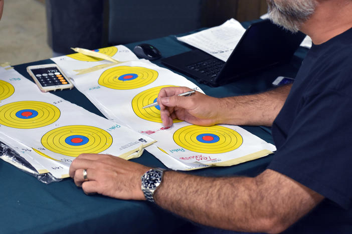 A volunteer scores the targets of several participants in the 11th District GOP's Fifth Annual Marksmanship Event and Barbecue