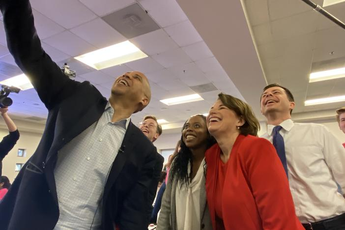 Sen. Cory Booker, Fair Fight Georgia's Esosa Osa, Sen. Amy Klobuchar and Mayor Pete Buttigieg smile for a selfie at a Fair Fight text bank contacting voters facing removal from Georgia's voter rolls.