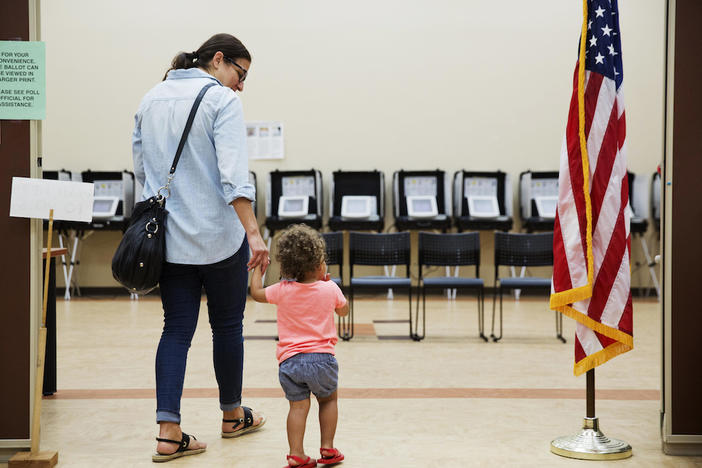 Melissa Painter walks with her one year-old daughter Elle to vote in Georgia's 6th Congressional District special election at a polling site in Sandy Springs, Ga., Tuesday, June 20, 2017.