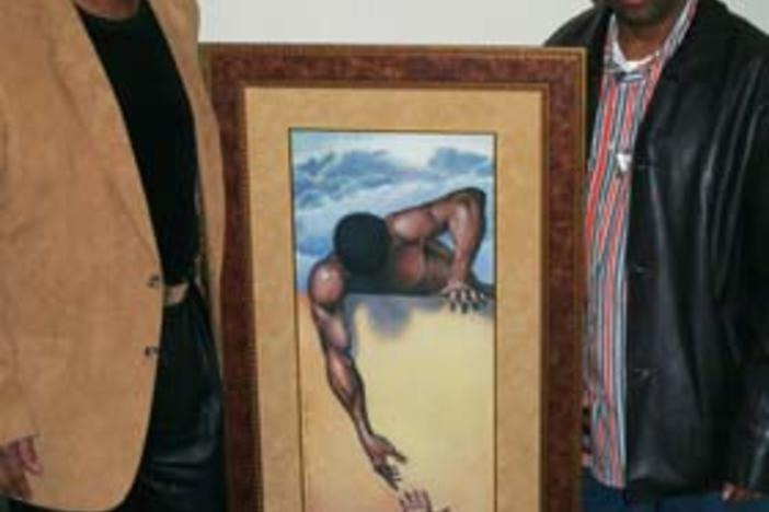 "Artist Gilbert Young pictured with actor, film director Spike Lee and ""He Ain't Heavy"" painting."