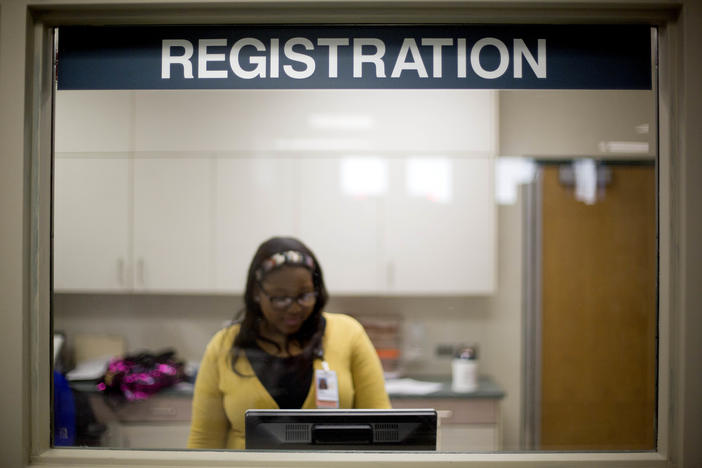 In this Friday, Jan. 24, 2014 photo, a worker is seen behind the registration window of the emergency room at Grady Memorial Hospital, in Atlanta. In two years, federal payments to hospitals treating a large share of the nation's poor will begin to evapor