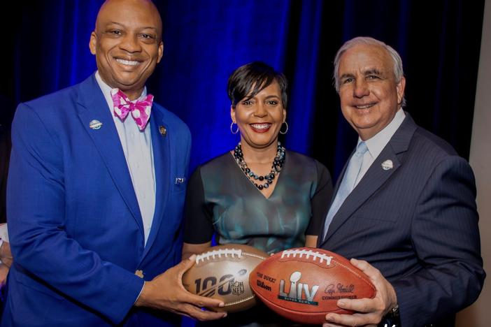 Oliver Gilbert (left) and Atlanta Mayor Keisha Lance Bottoms handoff the Super Bowl to Miami-Dade County Mayor Carlos Gimenez.
