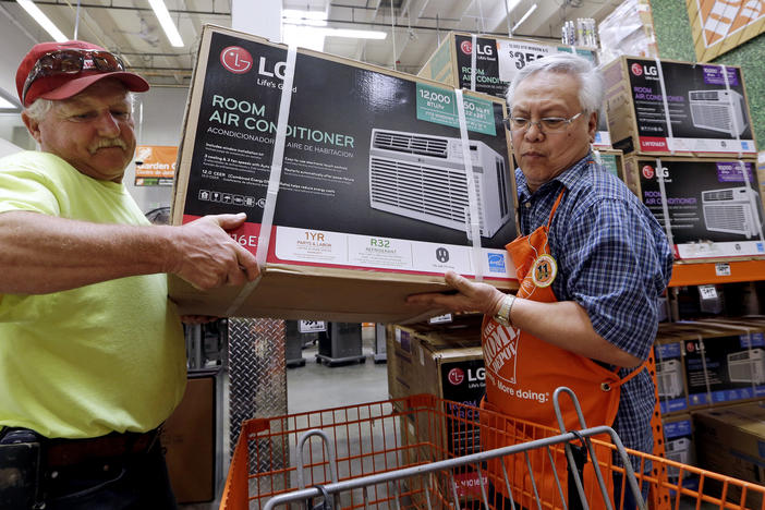 Home Depot store greeter Danny Olivar, right, helps a customer buying an air conditioner. A new study finds Georgians will need to adapt to more days of extreme heat in the coming decades.