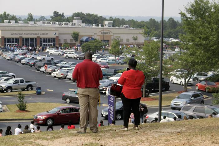 Thousands of job hunters wait in a mile-long line along Eisenhower Parkway for a warehouse job fair in Macon.