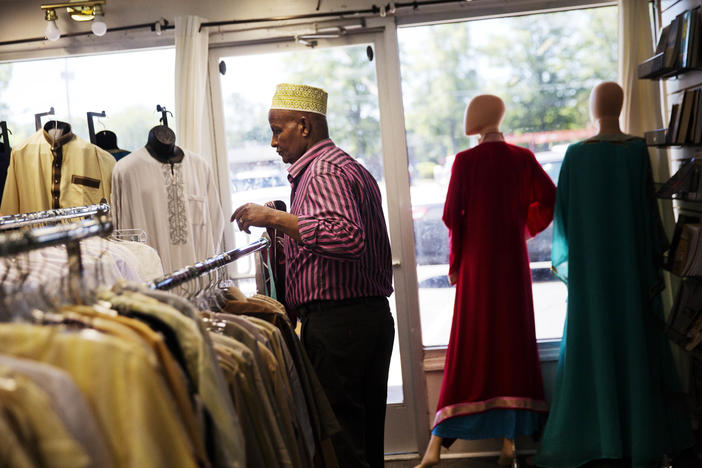 Mohamoud Saed, a refugee from Somalia, helps out in a friend's clothing store in Clarkston, Ga., Tuesday, May 2, 2017.