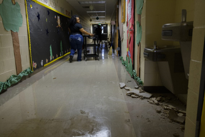 Pre-kindergarten teacher Jessica Beard walks past storm damage at Potter Street Elementary.