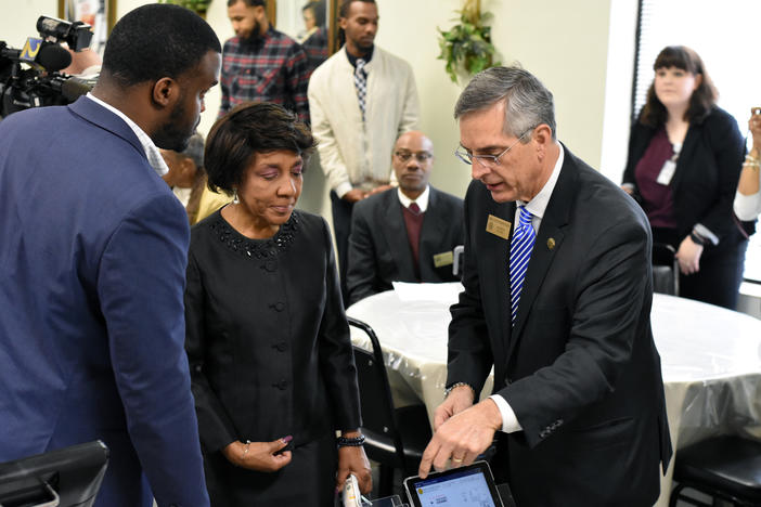 Rev. Bettye Holland Williams (center), president of the Concerned Black Clergy of Metro Atlanta, receives a demonstration of the new system from Secretary of State Brad Raffensperger and elections staff.