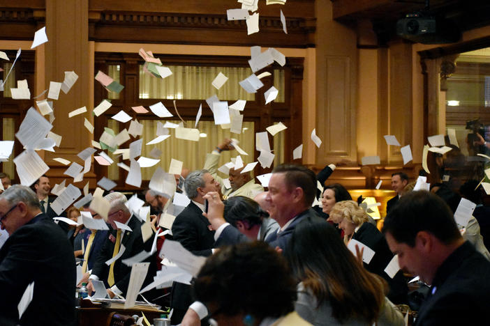Members of the House toss bills into the air as the clock strikes midnight and the legislature adjourns Sine Die ending the 2019 legislative session.