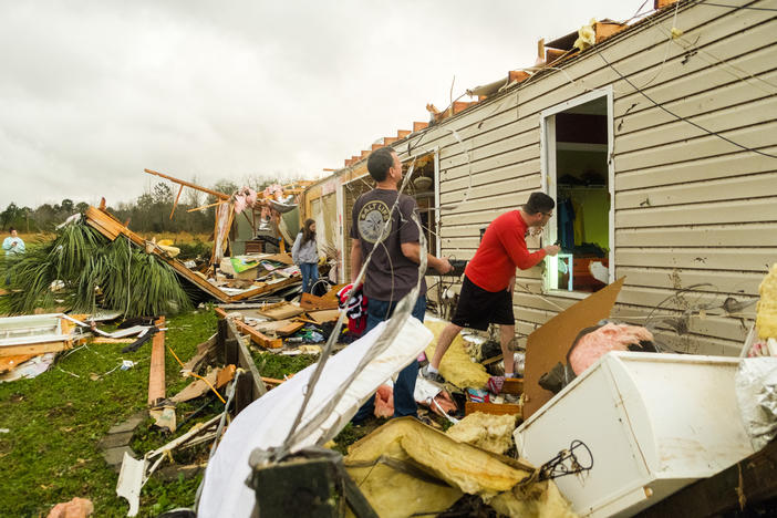 Neighbors look through a home just north of Fort Valley in Crawford County, destroyed by a tornado Sunday night.