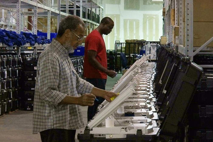 This Sept. 22, 2016 file photo shows employees of the Fulton County Election Preparation Center in Atlanta test electronic voting machines. A security researcher disclosed a gaping security hole at the outfit that manages Georgia's elections.