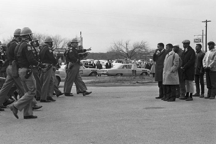Protesters, including John Lewis (tan trenchcoat), and police officers stand off on Bloody Sunday, March 7, 1965, in Selma, Alabama.