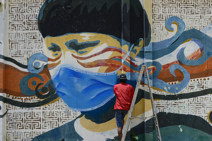 A street artist spray paints a protective face mask over an old mural featuring a Venezuelan Indigenous man, in Caracas, Venezuela, on Saturday. Globally, new daily cases hit an all time high, the World Health Organization reports.