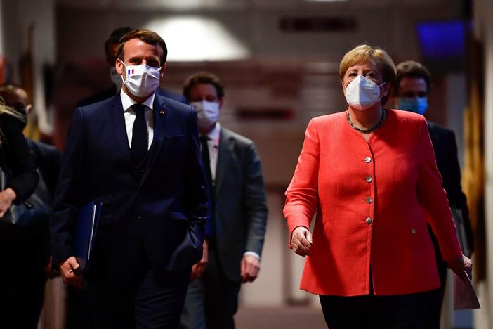 French President Emmanuel Macron and German Chancellor Angela Merkel arrive for a joint news conference at the end of the European summit at EU headquarters in Brussels on Tuesday.