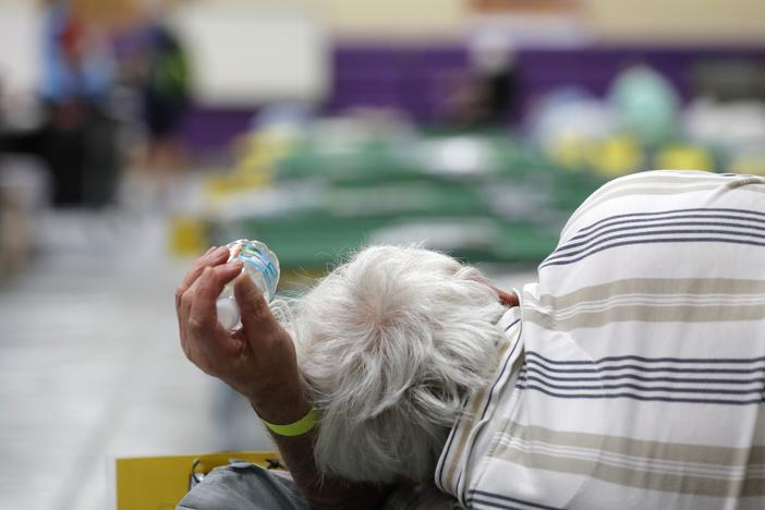 An evacuee lies on a cot at an evacuation shelter for people with disabilities in Stuart, Fla., in preparation for Hurricane Dorian on Sept. 1, 2019. Now, with the pandemic raging, officials across the South are trying to adjust their evacuation and shelter plans.