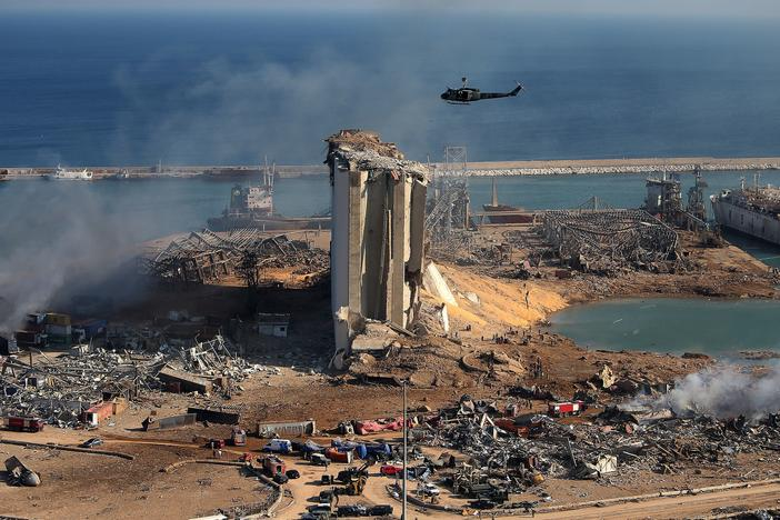 A helicopter hovers over damaged grain silos in Beirut's port on Wednesday, one day after a powerful explosion tore through Lebanon's capital.