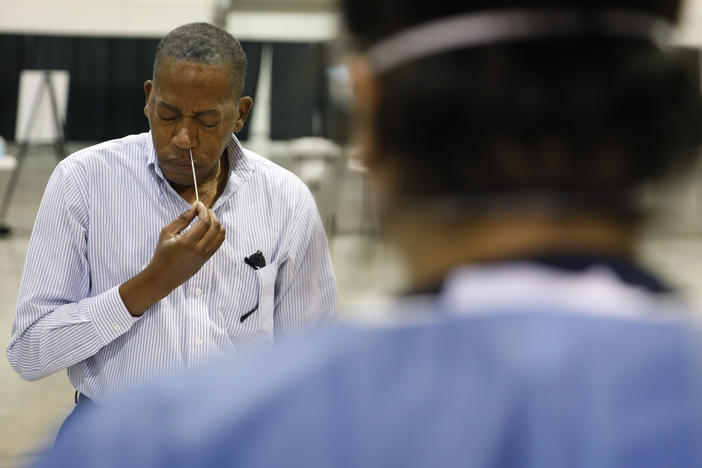 Clark County Commission Vice Chairman Lawrence Weekly swabs his nose while giving a coronavirus test to himself during a tour of setup at a temporary coronavirus testing site in Las Vegas on Aug. 3.