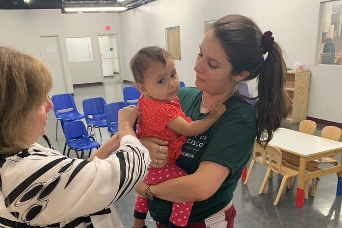 Dr. Goza listens to the lungs of a 2-year-old at Catholic Charities' Humanitarian Respite Center in McAllen, TX. After the toddler was released from CBP, she was sent to the emergency room with pneumonia and an undiagnosed congenital heart condition.