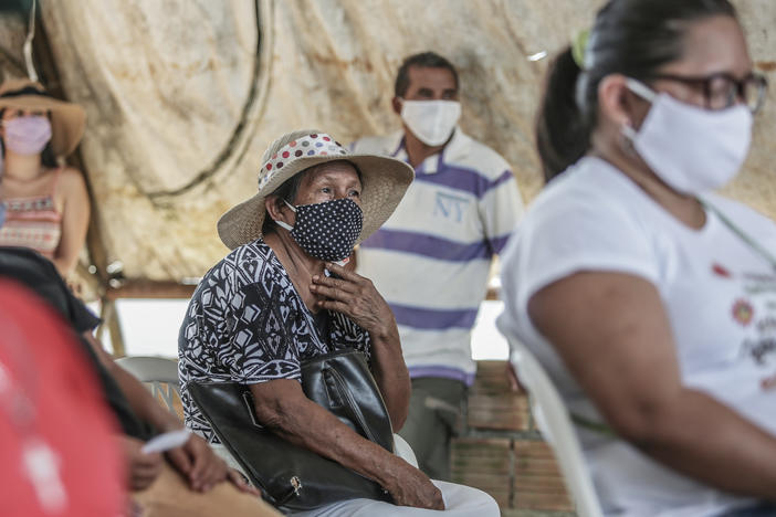People wait for a flu vaccine in May in Manaus, Brazil. The flu season had a surprisingly low count of influenza cases in the Southern Hemisphere, and researchers are trying to figure out the role coronavirus precautions might have played.