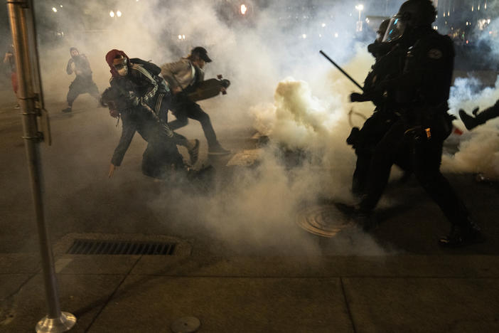 Protesters scramble to get away from approaching police firing tear gas and impact munitions to disperse protesters in downtown Portland during 4th of July demonstrations against systemic racism and police violence.