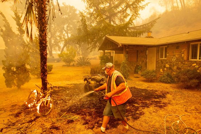 A Californian resident hoses down a burning bicycle and tree as flames from the Hennessey Fire approach a property in the Spanish Flat area of Napa, Calif., on Aug. 18.
