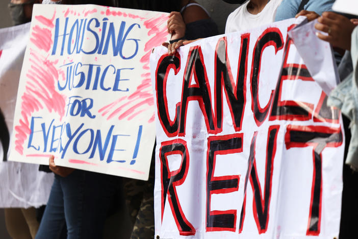 Demonstrators hold up signs as they gather at Brooklyn Housing court during a 'No Evictions, No Police' national day of action in New York City.
