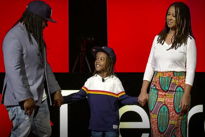 Shaka Senghor (left), Ebony Roberts (right), and their son Sekou speak on the TED stage.