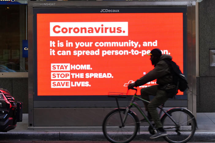 A person on a bike rides by a sign in New York City urging people to stay home in May. As the pandemic drags on, some workers are facing tough choices — balancing potential risks of unwittingly spreading the disease against the possibility of losing pay during a quarantine.